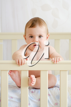 naked child sitting in a crib and looking at the camera