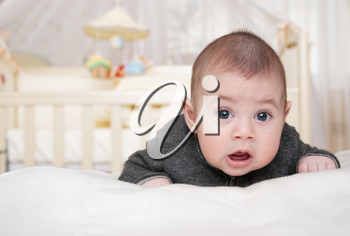 toothless baby lies on a stomach and with astonishment looks