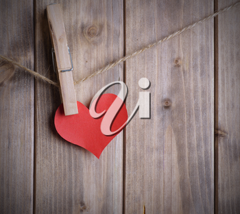 red heart made of paper with clothespin hanging on a rope and wooden planks background with space for text