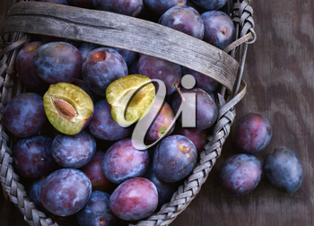 Fresh ripe black plums in a basket closeup