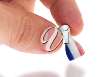 Hand holding wooden pawn with a flag painting, selective focus, France