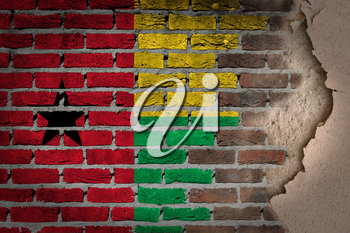 Dark brick wall texture with plaster - flag painted on wall - Guinea Bissau
