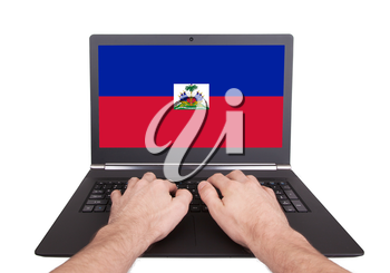 Hands working on laptop showing on the screen the flag of Haiti