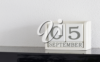 White block calendar present date 5 and month September on white wall background