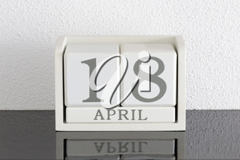 White block calendar present date 18 and month April on white wall background
