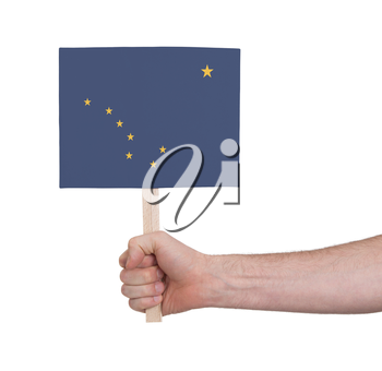 Hand holding small card, isolated on white - Flag of Alaska