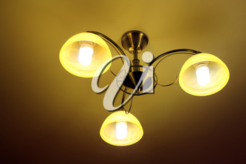 Beautiful chandelier with three bright plafonds under the ceiling
