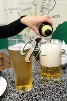 image of woman' s hand pouring beer in a glass