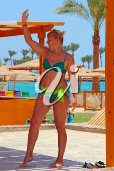 Woman dancing in resort. Beach clothes. Girl in dance. Female dancing in swimsuit. Woman enjoying dancing while summer holidays