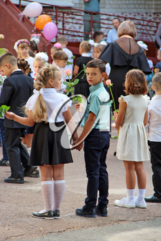 Study season at the Ukrainian school. Knowledge Day celebration in the city of Chernihiv. Children at the gala event. Holiday of knowledge. Boy and girl holding hands