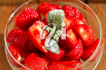 sliced ripe strawberries in a transparent bowl