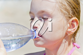 Cute blond girl with drinking water from bottle