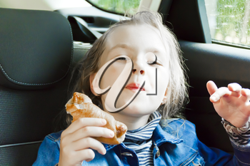 Eating cute girl with blond wet hair sitting inside car