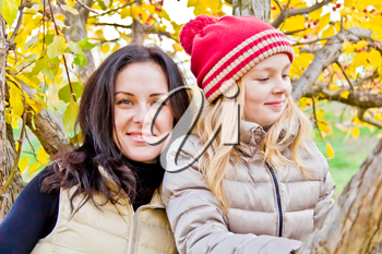 Photo of mother and daughter in autumn sitting on tree