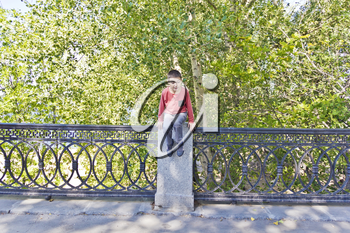Teenager boy is jumping on green summer embankment
