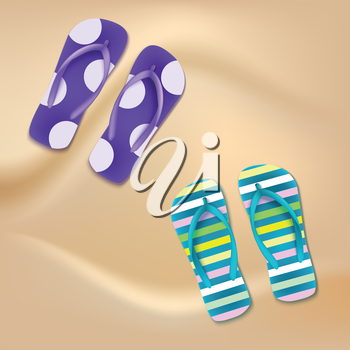 Colored beach slippers with pattern on the sandy background
