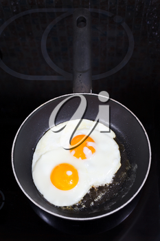 two prepared fried eggs in frying pan on electric stove