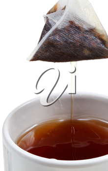 removing of tea bag from mug with brewing tea close up isolated on white background