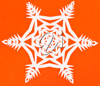 hand made cut out white snowflake on orange paper