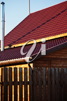 wood fence, chimney,red tile of new wooden house in country village