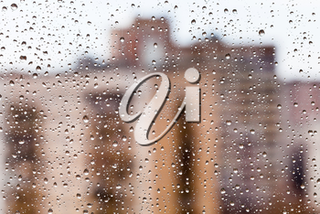 rain drops on glass with brick urban houses background