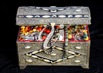 ancient east treasure chest with antique jewelry on black textile