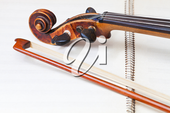 fiddle bow and scroll on music book close up