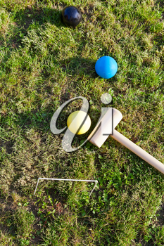 top view of balls and mallet for game of croquet on green lawn in summer day