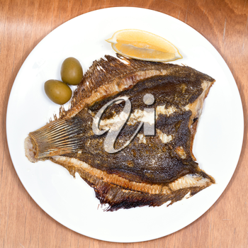 top view of fried sole fish on white plate on wooden table