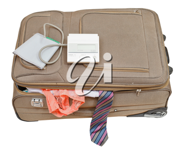 sphygmomanometer on suitcase with male tie and female panties isolated on white background