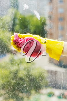 hand in yellow rubber glove washing window glass by soapy water