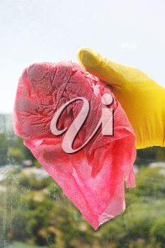 hand in yellow rubber glove washing window glass by wet rag