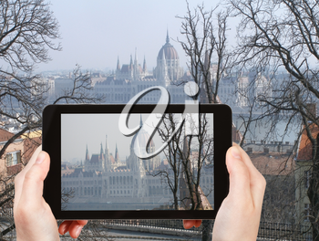 travel concept - tourist taking photo of Hungarian Parliament Building in spring morning on mobile gadget, Hungary