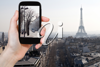 travel concept - tourist taking photo of Avenues in Paris in early spring on mobile gadget, France