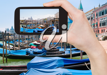 travel concept - tourist taking photo of gondolas near Piazza San Marco in Venice, Italy on mobile gadget