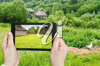 travel concept - tourist takes picture of backyard in peasant household in russian village on smartphone, Smolensk region