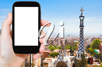 travel concept - tourist photograph skyline of Barcelona city, Spain on smartphone with cut out screen with blank place for advertising logo