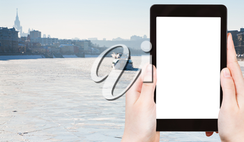 travel concept - tourist photograph iceboat on frozen Moscow river in sunny winter day on tablet pc with cut out screen with blank place for advertising logo