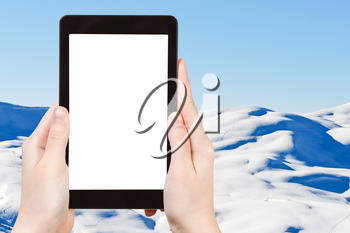 travel concept - tourist photograph skiing tracks on snow Alps mountains in Portes du Soleil region, Evasion - Mont Blanc, France on tablet pc with cut out screen with blank place for advertising logo
