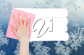 weather concept - hand deletes winter snoflakes on window by pink rag from image and white empty copy space are appearing