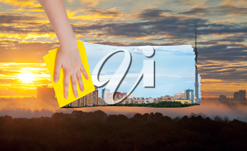 weather concept - hand deletes yellow sunrise over city by yellow cloth from image and day cityscape is appearing