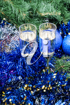 Christmas still life - Two glasses of champagne with blue Xmas baubles and tinsel and on Christmas tree background