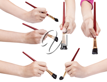 set of hands with flat art paintbrushes with black painted tips isolated on white background