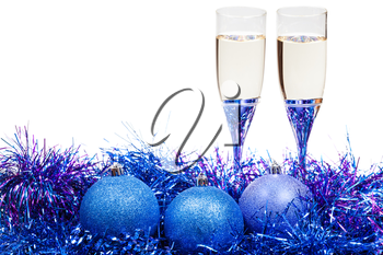 two glasses of champagne at blue and violet Christmas balls and tinsel isolated on white background