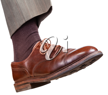 male right foot in brown shoe takes a step isolated on white background