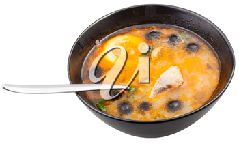 above view of Solyanka russian traditional spicy and sour soup with fish in bowl with spoon isolated on white background