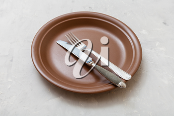 food concept - brown plate with parallel knife, spoon on gray concrete surface