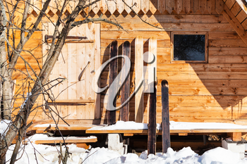 wide hunter skis in front of wooden cottage in sunny winter day in russian village in Smolensk region of Russia