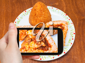 travel concept - tourist photographs meat ragu stuffed rice balls arancini on plate (traditional sicilian street food) in Sicily Italy on smartphone