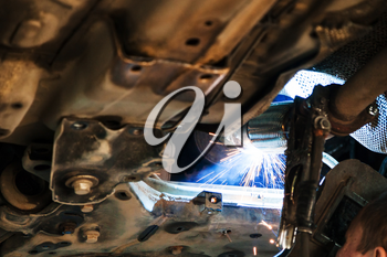 repairing of corrugation muffler of exhaust system in car workshop - welder welds the silencer on car by argon welding
